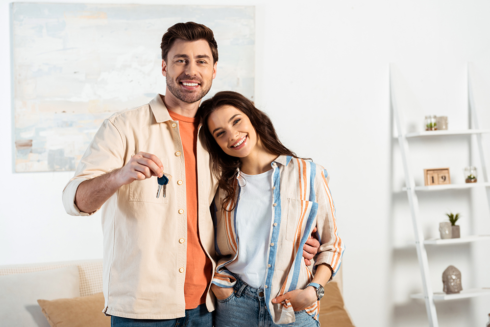 Couple holding the keys to their new house after getting a home inspection